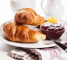 Fresh croissants with butter and a glass of milk on a plate
